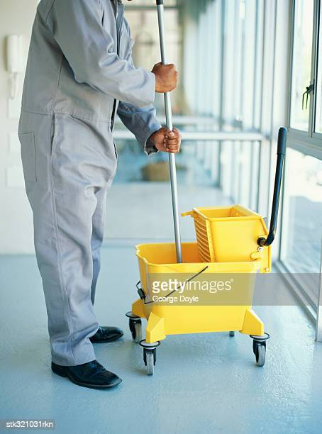 man standing in a corridor with a mop and a bucket
