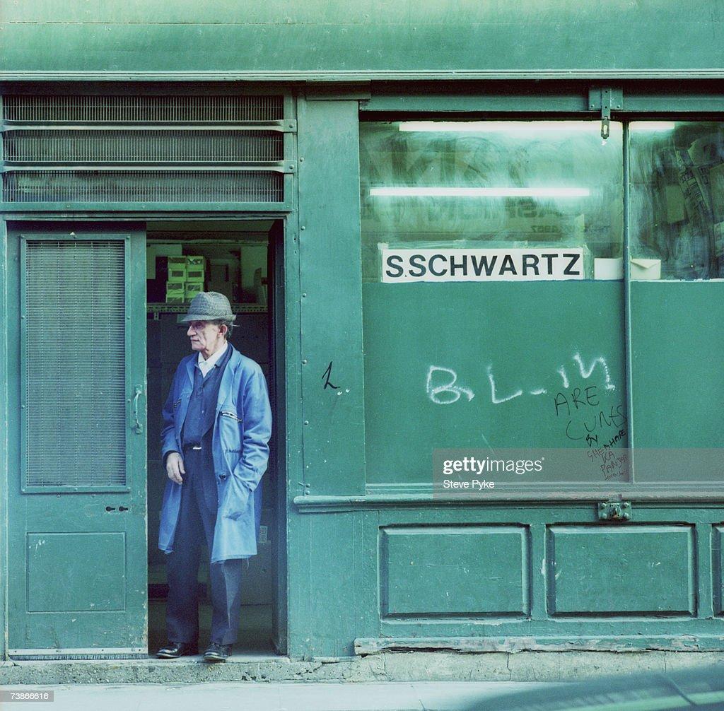 A man standing in a shop doorway on Brick Lane, east London, 1992.