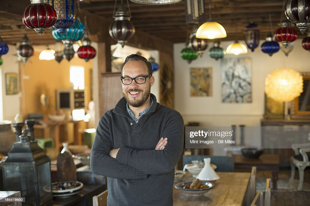 A man standing in a shop full of antique and decorative objects. Antique shop displays. Lighting, glass shades and furniture.