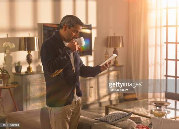 Man standing in a sunny room looking at an iPad