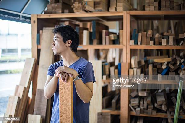 A man standing in a workshop looking out