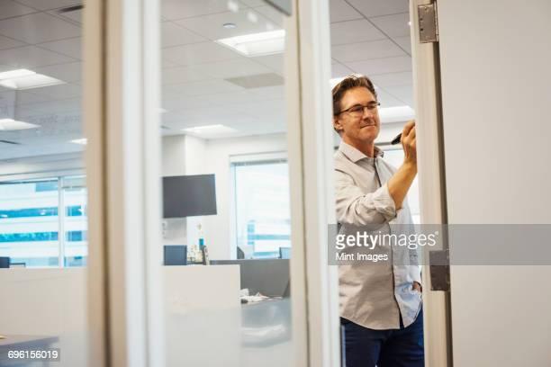 A man standing in an office writing on a whiteboard, seen through a doorway.