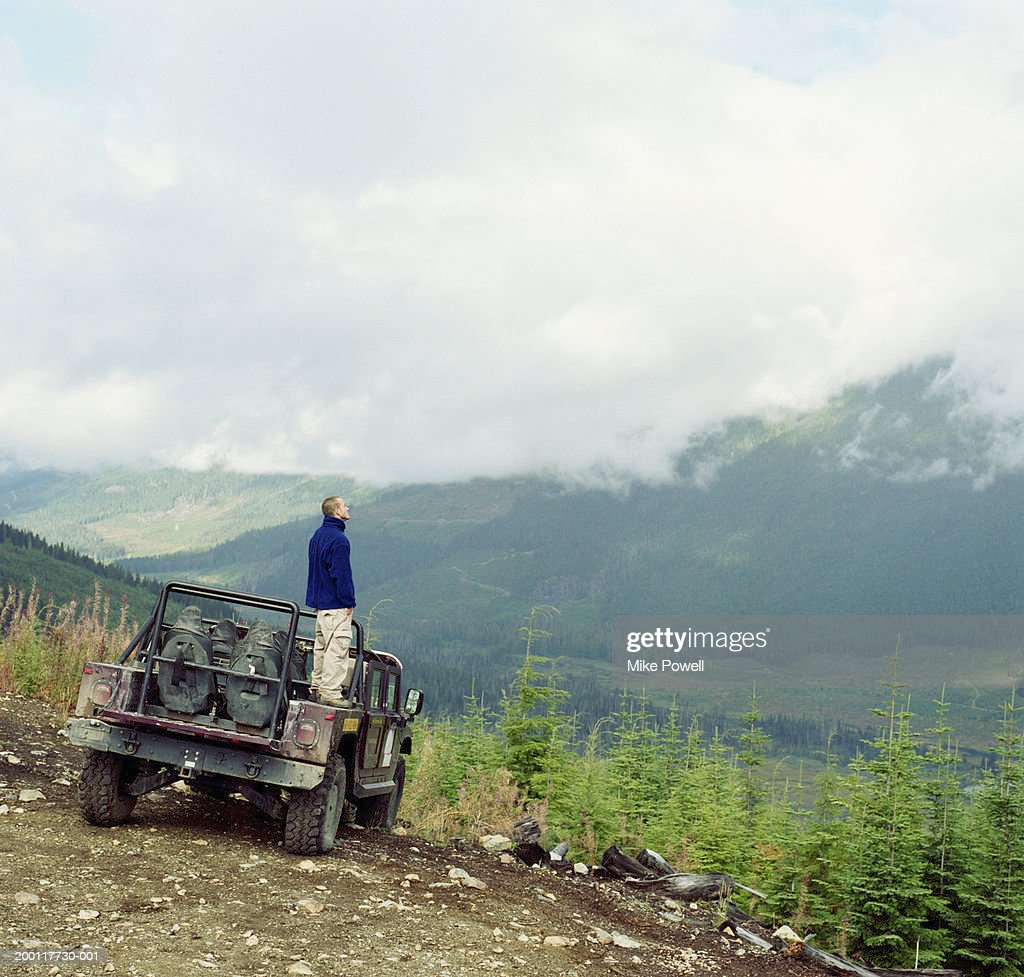 Man standing in back of off road vehicle, looking at mountain view : Stock Photo