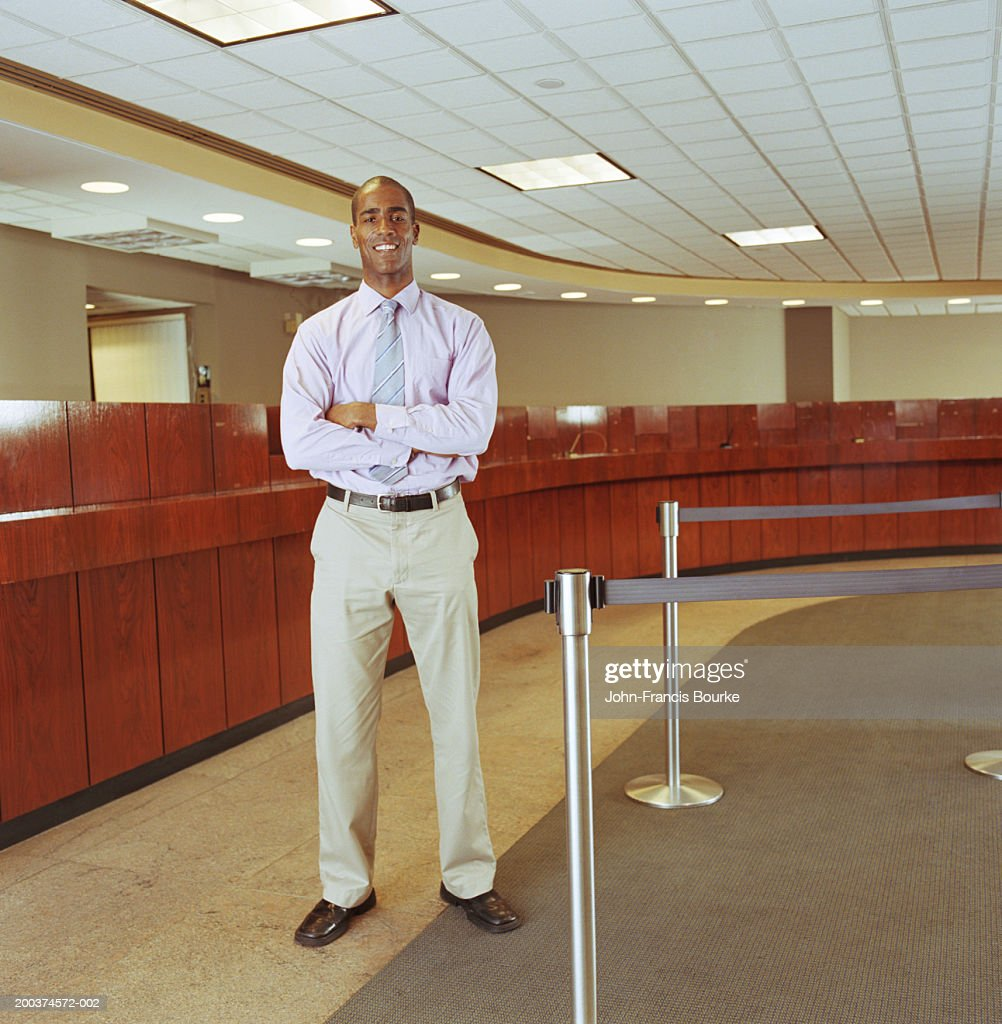 Man standing in bank with arms crossed, portrait