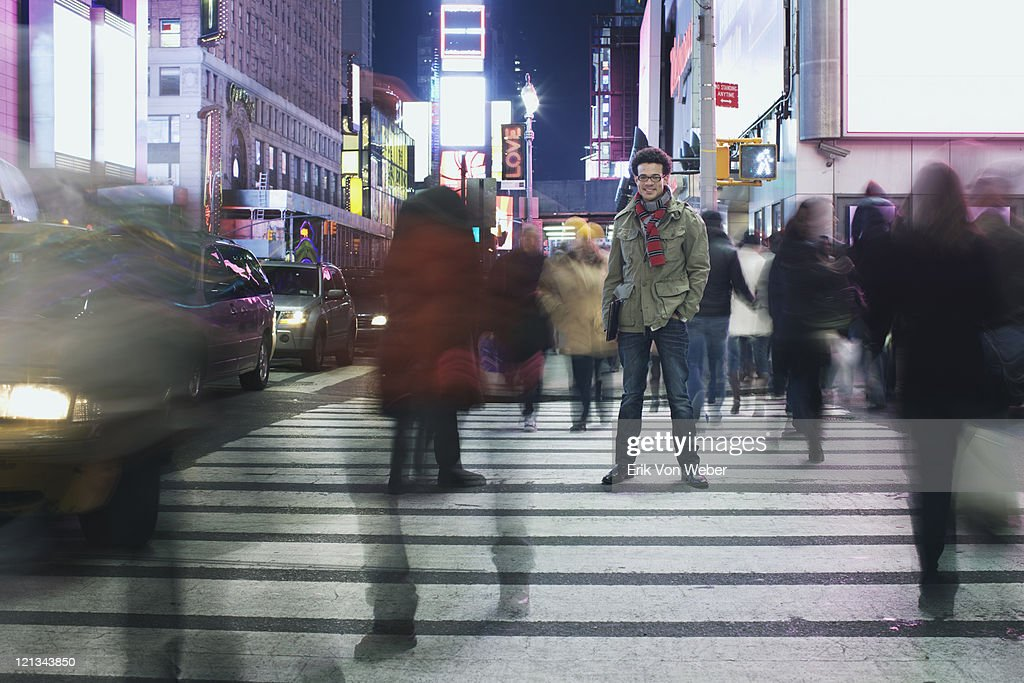 Man standing in busy intersection in Times Square : Stock Photo