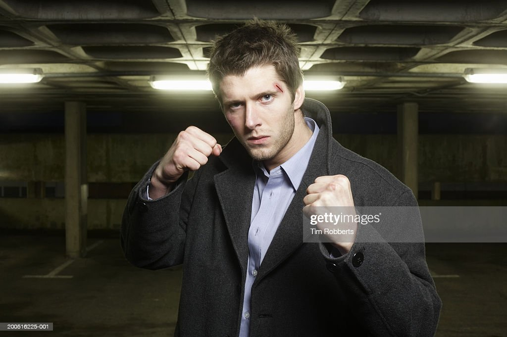 Man standing in carpark with raised fists : Stock Photo