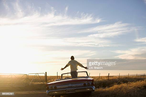 Man standing in convertible in countryside