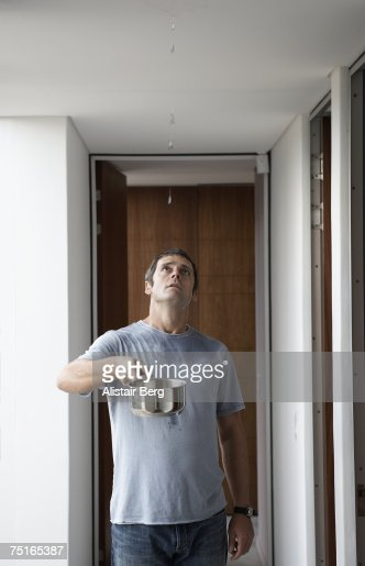Man standing in corridor, holding saucepan under leak in ceiling, looking up