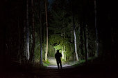 Man standing in dark forest at night with flashlight and hoodie on head. Mystical and abstract outdoor photo of Swedish nature and landscape at winter.