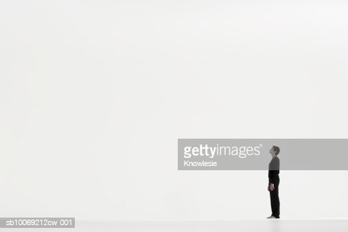 Man standing in distance against white background, side view : Stock Photo