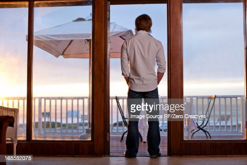 Man standing in doorway of patio