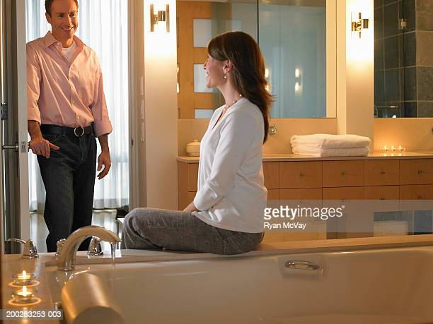Man standing in doorway, smiling at woman sitting on edge of bathtub
