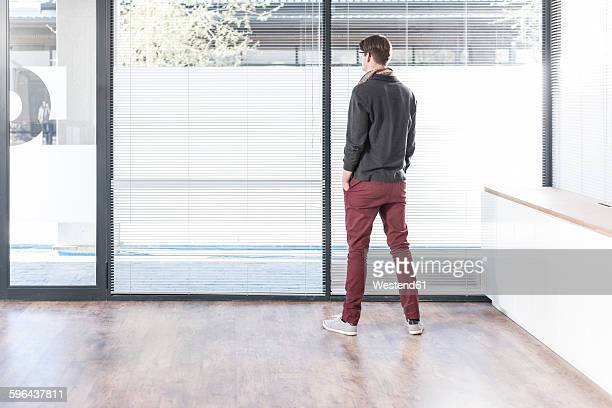 Man standing in empty office looking out of window