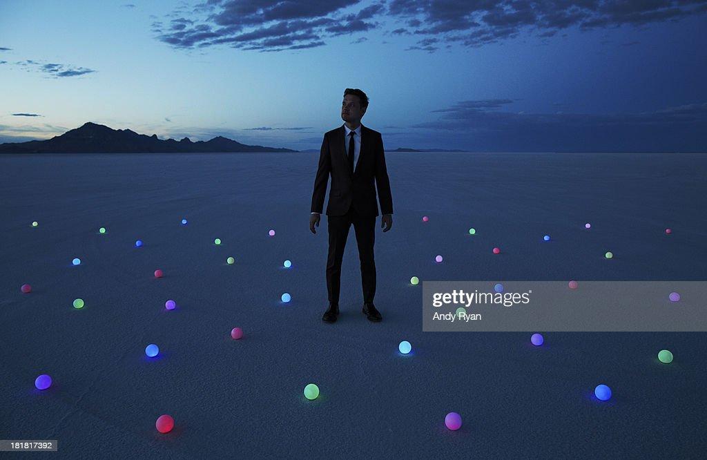 Man standing in field of glowing orbs in desert.