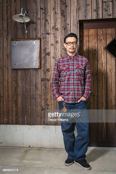 A man standing in front of a wooden building