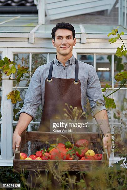Man standing in front of greenhuse with produce