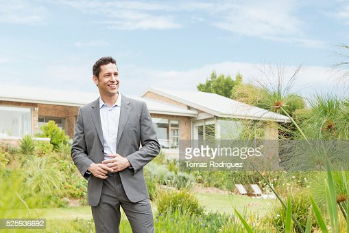Man standing in front of modern house : Stock Photo