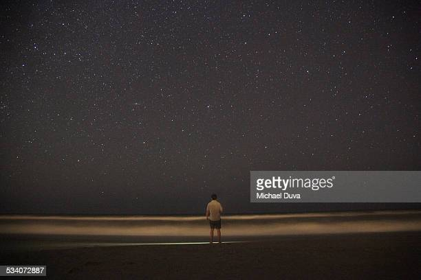 man standing in front of ocean and stars at night
