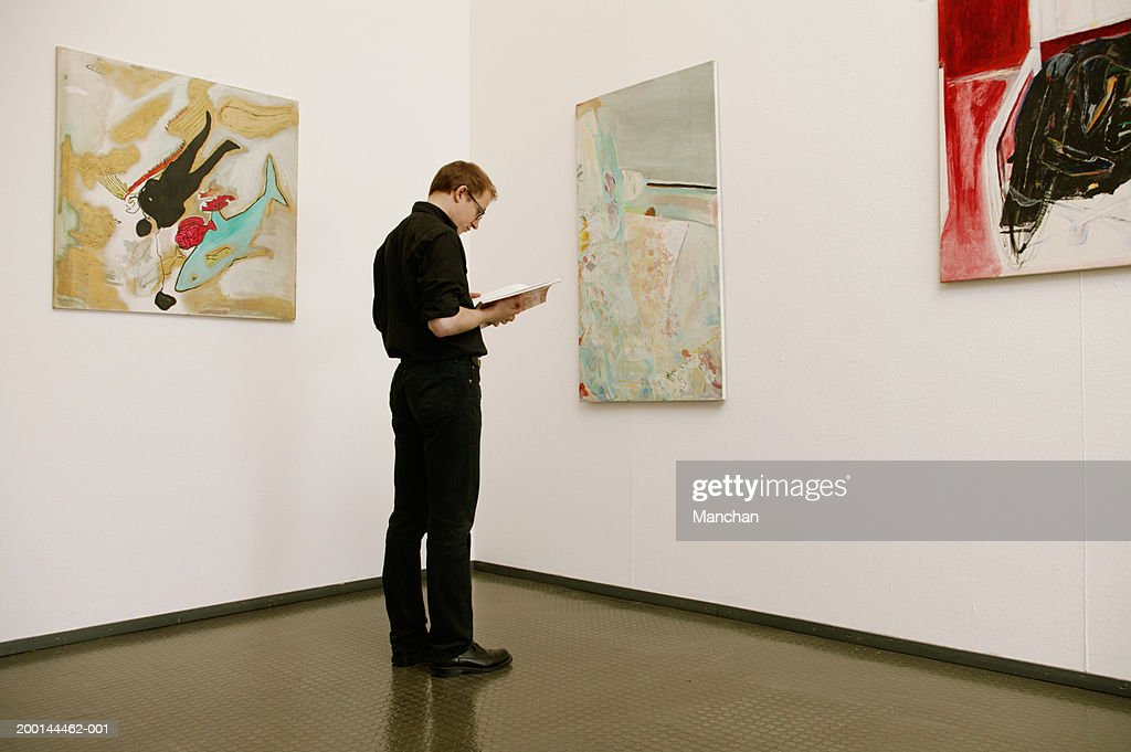 Man standing in front of painting looking down at book : Stock Photo