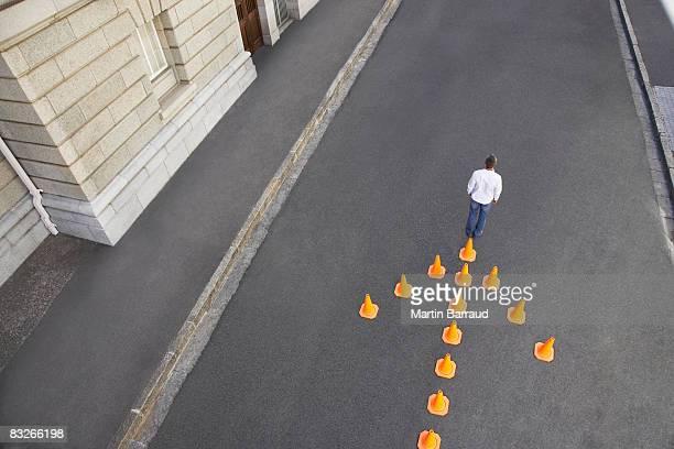 男性の前で交通コーンズの矢印型