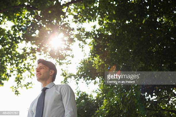 Man standing in front of trees with sun flare.