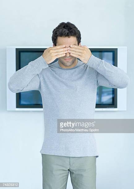 Man standing in front of wide screen TV, hands over eyes