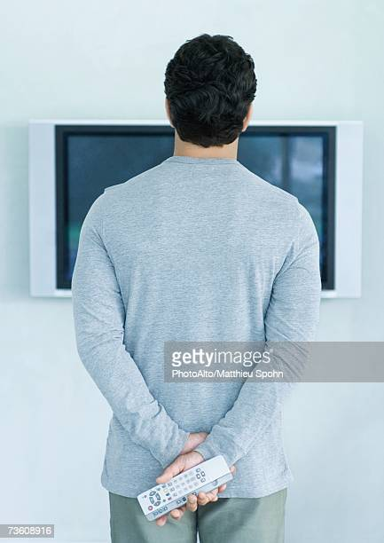 Man standing in front of widescreen TV, holding two remote controls, rear view