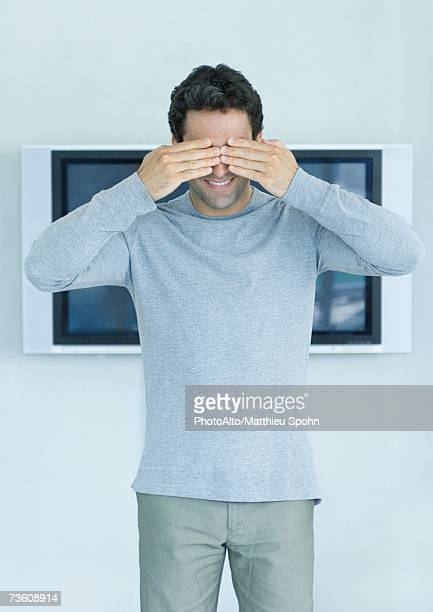 Man standing in front of widescreen TV on wall, hands covering eyes