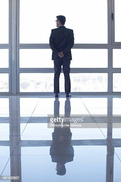 Man standing in front of window, looking at view