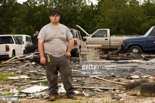 Man standing in front of wrecking yard : Stock Photo