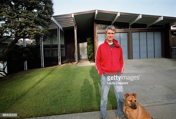 Man standing in front yard with dog