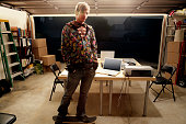 Man standing in garage with table of laptops, portrait
