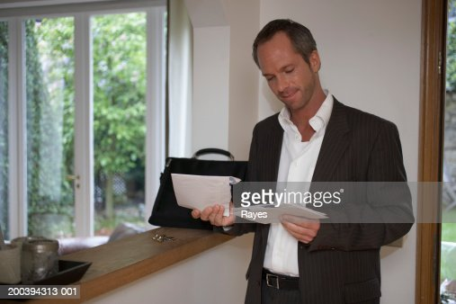 Man standing in hallway looking at post, smiling : Stock Photo