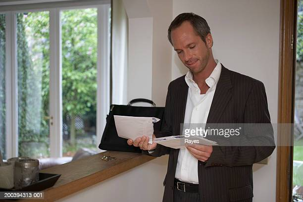 Man standing in hallway looking at post, smiling