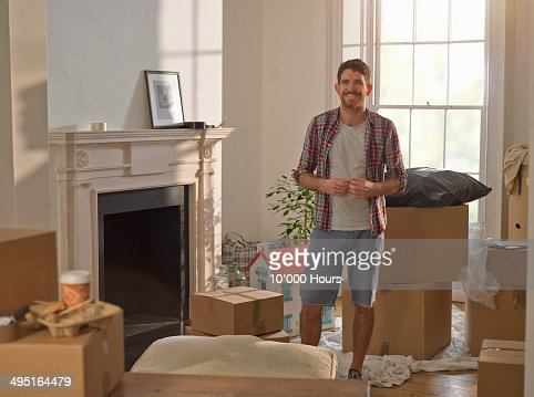 A man standing in his new home surrounded by boxes
