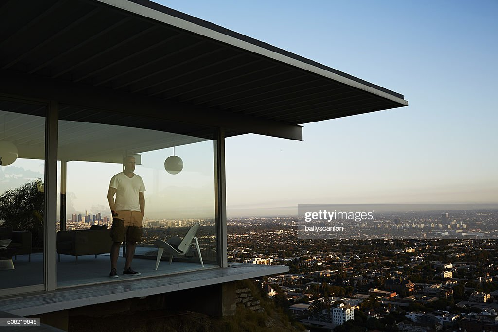 Man Standing In House Overlooking Los Angeles. : Stockfoto