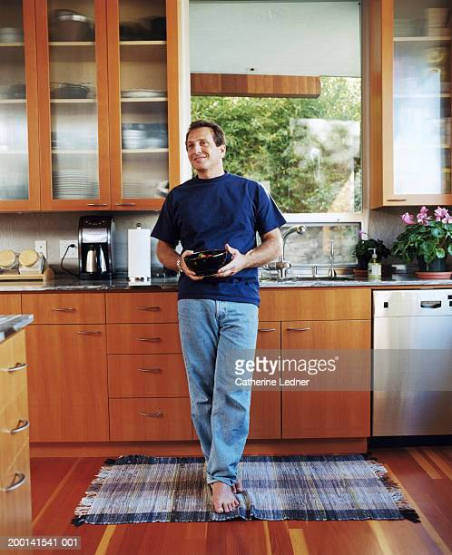 Man standing in kitchen, holding bowl of strawberries