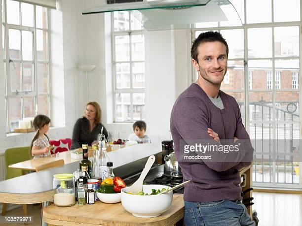 Man standing in kitchen, smiling, (portrait)