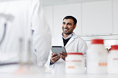 Man standing in laboratory, using tablet
