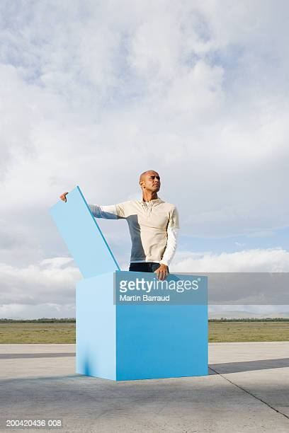 Man standing in large blue open box