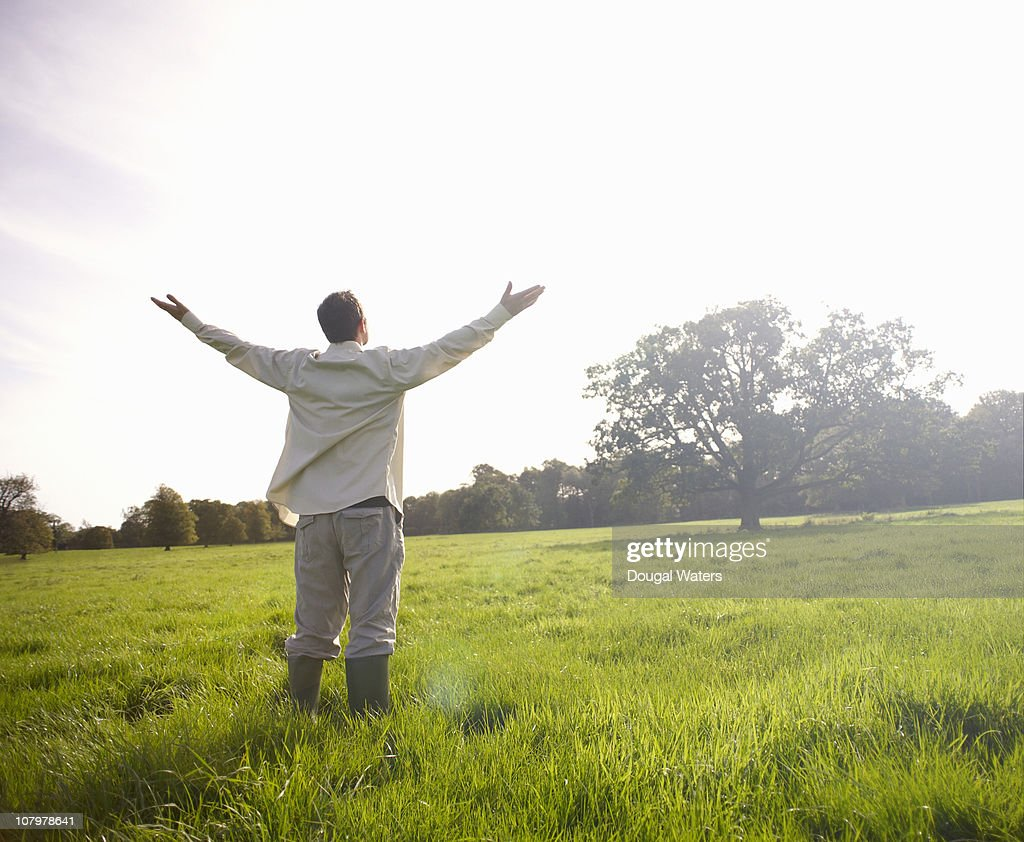 Man standing in meadow with arms stretched. : Stock Photo
