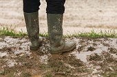 A person in rubber boots standing in the mud.