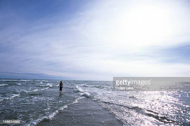 Man standing in ocean of Grenen, Denmarks northern tip, near Skagen.