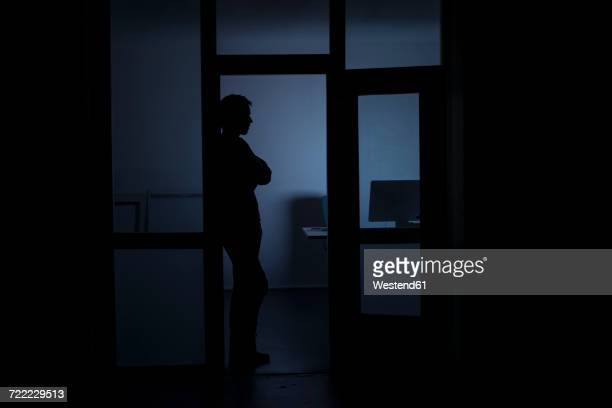 Man standing in office at night