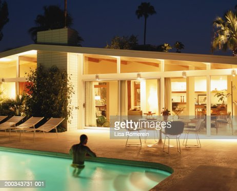 Man standing in pool, house lit at night : Stock Photo
