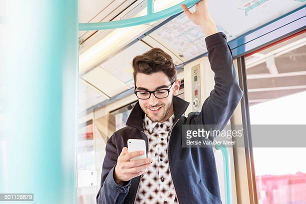 Man standing in public transport looking at phone.