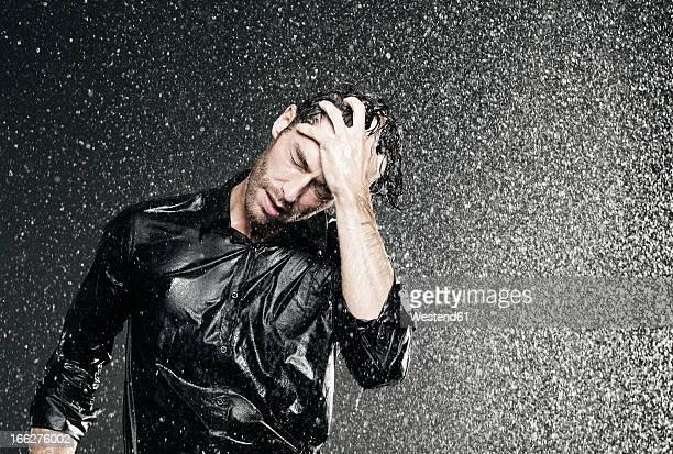 Man standing in rain, head in hand.