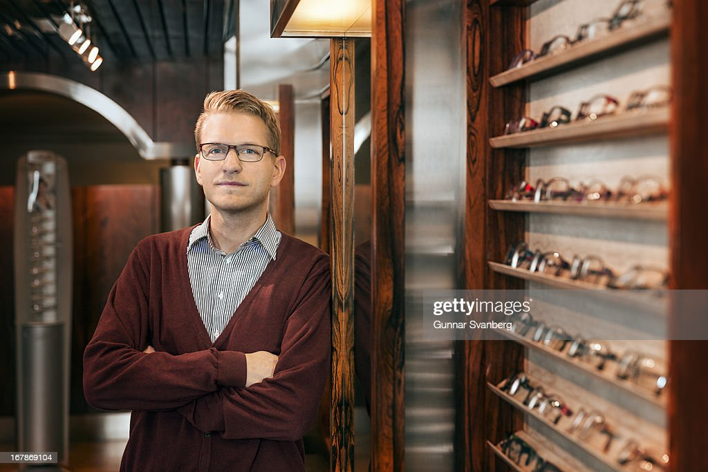 Man standing in shop surrounded by glasses. : Stock Photo