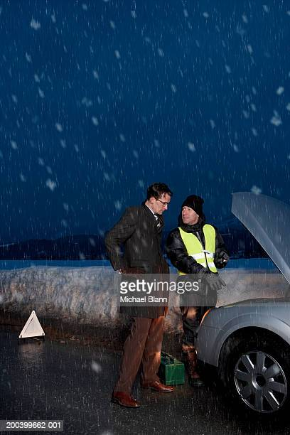 Man standing in snow with mechanic pointing to car engine, night