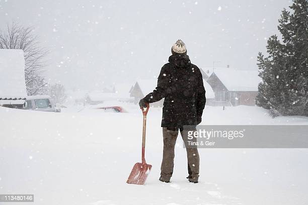 Man standing in snow with shovel